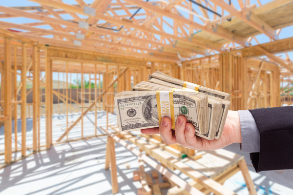 Hand With Stacks of Cash On Site Inside New Home Construction Fr Stock photo © feverpitch