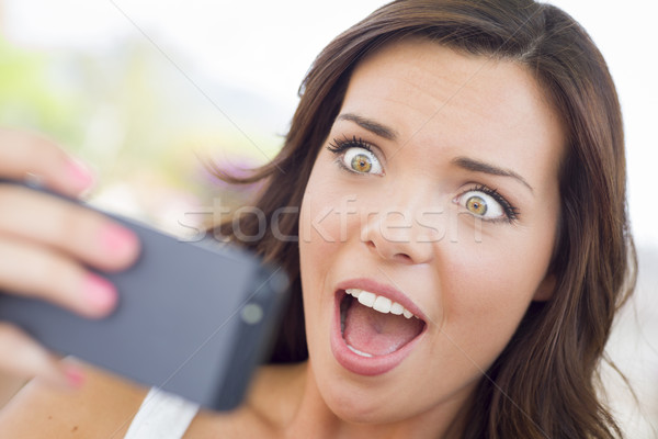 Shocked Young Adult Female Reading Cell Phone Outdoors Stock photo © feverpitch