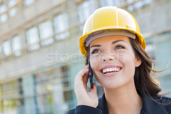 Young Female Contractor Wearing Hard Hat on Site Using Phone Stock photo © feverpitch