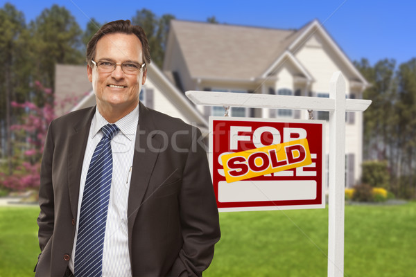 Male Real Estate Agent in Front of Sold Sign and House Stock photo © feverpitch