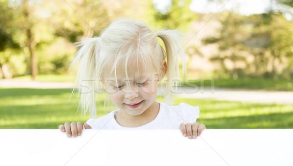 Aranyos kislány tart fehér tábla szoba szöveg Stock fotó © feverpitch