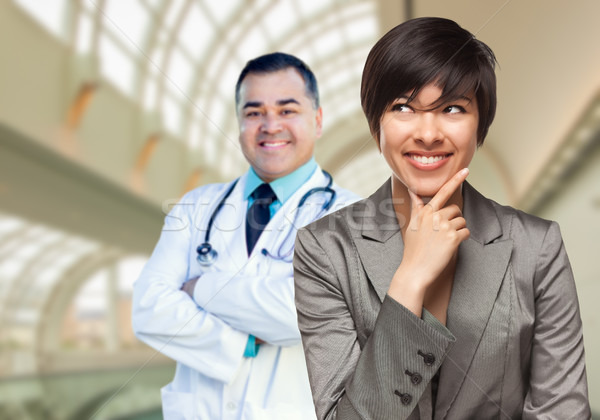 Male Doctor Stands Behind Woman Looking To Side Inside Hospital Stock photo © feverpitch