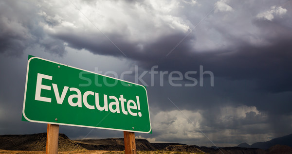 Evacuate Green Road Sign and Stormy Clouds Stock photo © feverpitch