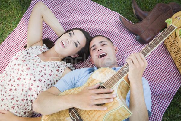 Halfbloed paar park spelen gitaar zingen Stockfoto © feverpitch