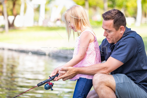 Young Caucasian Father and Daughter Having Fun Fishing At The La Stock photo © feverpitch