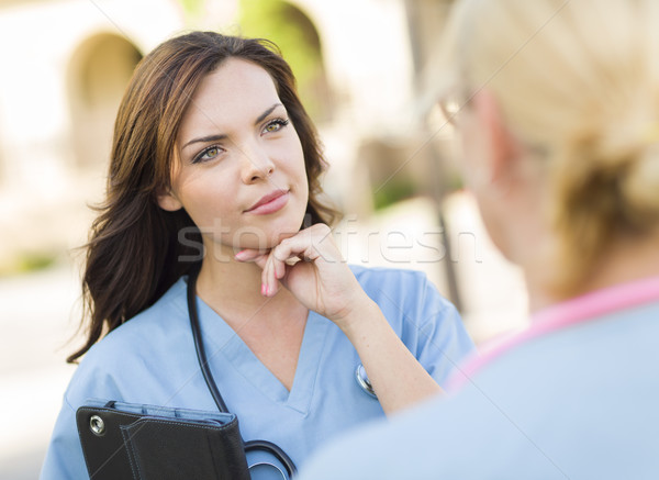 Stock photo: Two Young Adult Female Doctors or Nurses Talking Outside