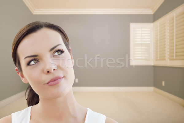 Daydreaming Young Woman in Empty Grey Room Stock photo © feverpitch