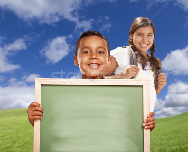 Hispanic Boy and Girl In Field Holding Blank Chalk Board Stock photo © feverpitch