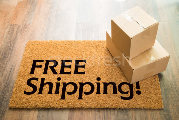 Free Shipping Welcome Mat On Wood Floor With Shipment of Boxes Stock photo © feverpitch