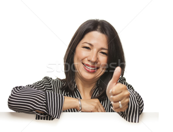 Mixed Race Woman Leaning on Blank White Sign with Thumbs Up Stock photo © feverpitch