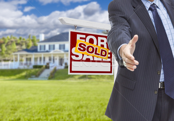 Agent Reaches for Handshake, Sold Sign and House Behind Stock photo © feverpitch