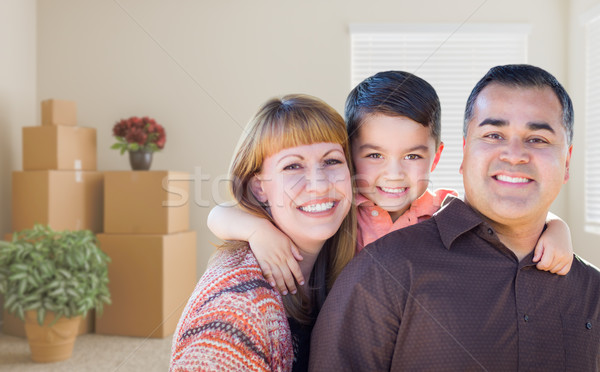 Mixed Race Family with Baby in Room with Packed Moving Boxes Stock photo © feverpitch