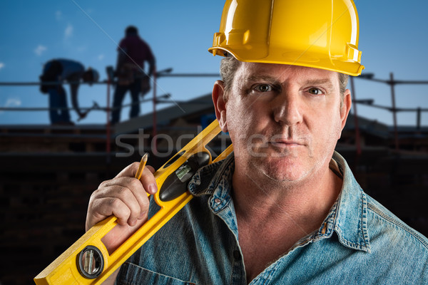 Serious Contractor in Hard Hat Holding Level and Pencil At Const Stock photo © feverpitch