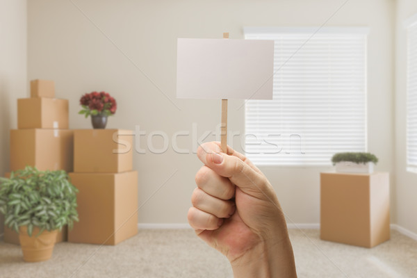 Hand Holding Blank Sign in Empty Room with Packed Moving Boxes Stock photo © feverpitch