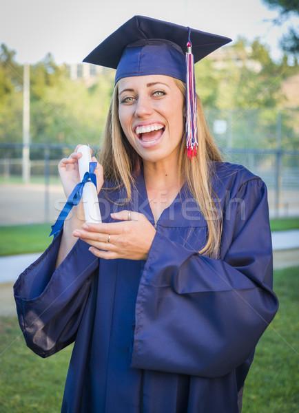 Kifejező fiatal nő tart diploma sapka talár Stock fotó © feverpitch