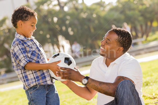 Father Hands New Soccer Ball to Mixed Race Son Stock photo © feverpitch
