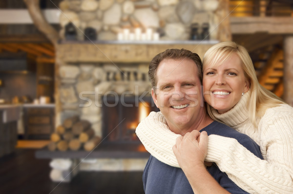 Affectionate Couple at Rustic Fireplace in Log Cabin Stock photo © feverpitch