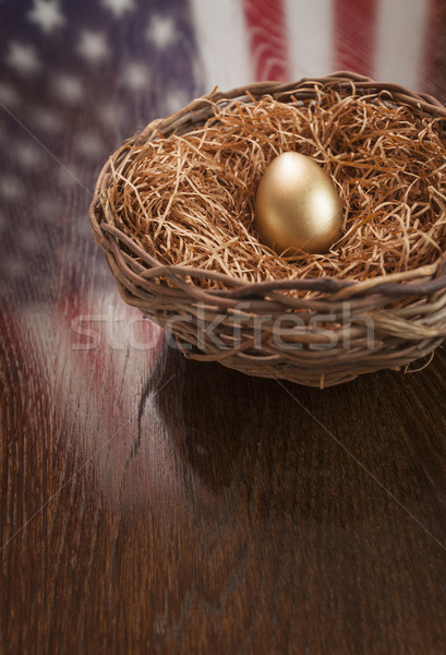 Golden Egg in Nest with American Flag Reflection on Table Stock photo © feverpitch