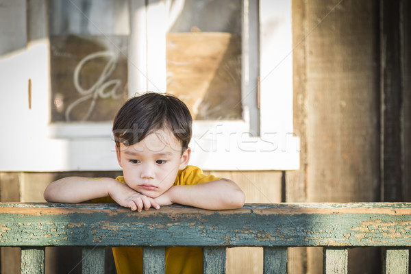 Melancholy Mixed Race Boy Leaning on Railing Stock photo © feverpitch
