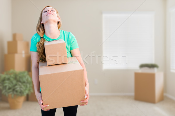 Tired Young Adult Woman Holding Moving Boxes In Empty Room In A  Stock photo © feverpitch