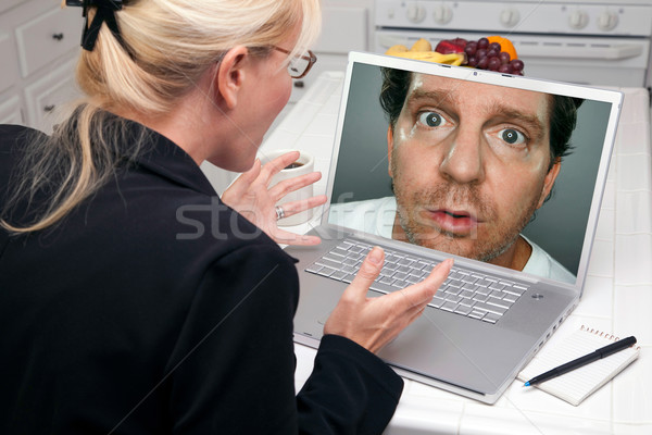 Excited Woman In Kitchen Using Laptop - Intrusion of Privacy Stock photo © feverpitch