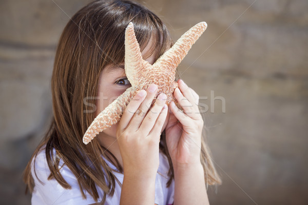 Young Girl Playing with Starfish Stock photo © feverpitch