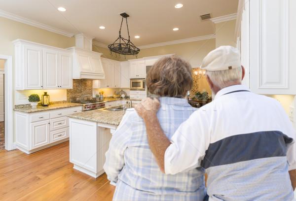 Stock photo: Senior Couple Looking Over Beautiful Custom Kitchen