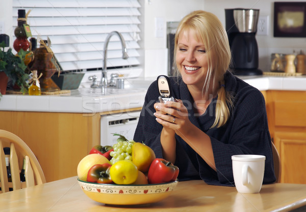 Stock photo: Woman In Kitchen Using Cell Phone