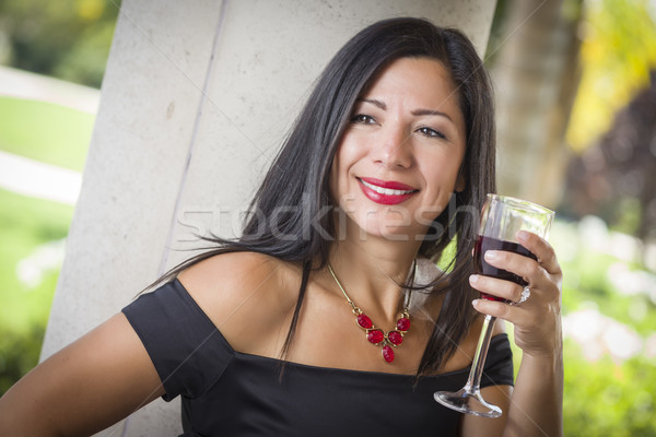 Attractive Hispanic Woman Portrait Outside Enjoying Wine Stock photo © feverpitch