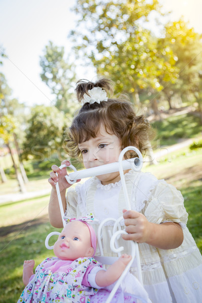 Adorable Young Baby Girl Playing with Baby Doll and Carriage Stock photo © feverpitch