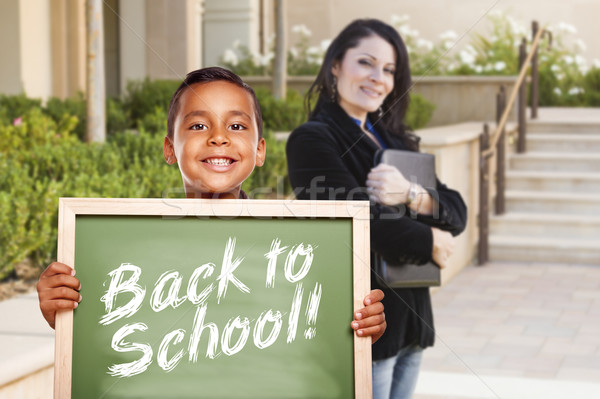 Boy Holding Back To School Chalk Board with Teacher Behind Stock photo © feverpitch