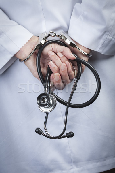 Female Doctor or Nurse In Handcuffs Holding Stethoscope Stock photo © feverpitch
