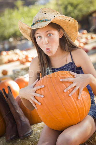 Preteen Girl Holding A Large Pumpkin at the Pumpkin Patch