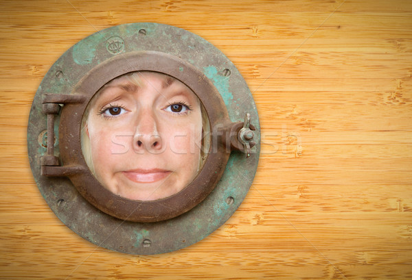 Stock photo: Antique Porthole on Bamboo Wall with Funky Woman Looking Through