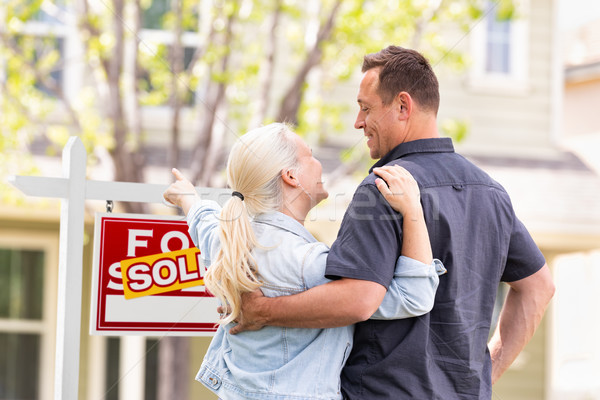 Caucasian Couple Facing and Pointing to Front of Sold Real Estat Stock photo © feverpitch