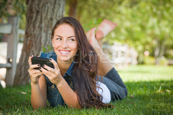 Attractive Happy Mixed Race Young Female Texting on Her Cell Pho Stock photo © feverpitch
