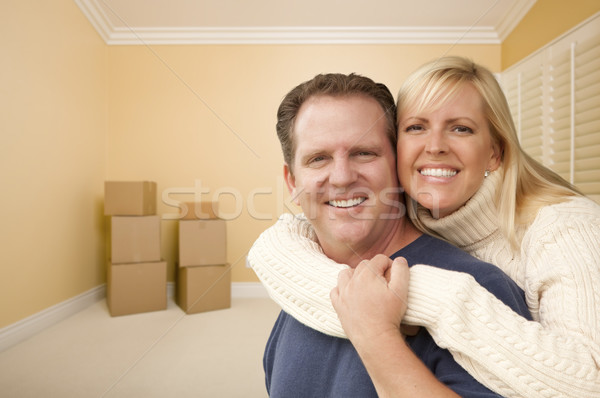 Happy Affectionate Couple in Room of New House with Boxes Stock photo © feverpitch