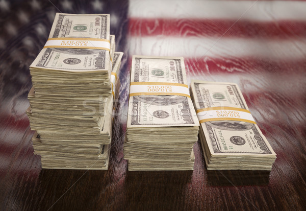 Stock photo: Thousands of Dollars with Reflection of American Flag on Table