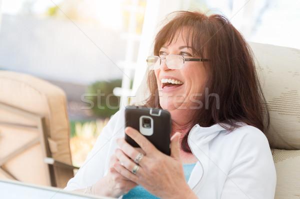 Vonzó középkorú nő nevet okos okostelefon belső udvar Stock fotó © feverpitch