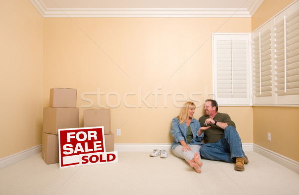 Couple on Floor Near Boxes and Sold Real Estate Signs Stock photo © feverpitch