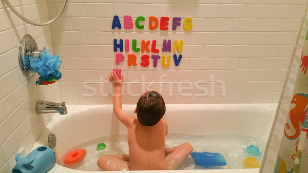 Stock photo: Young Boy Having Fun With The Alphabet On Wall At Bath Time