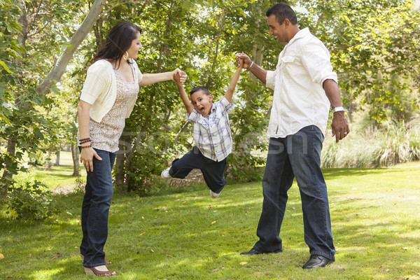 Hispanic Mother and Father Swinging Son in the Park Stock photo © feverpitch