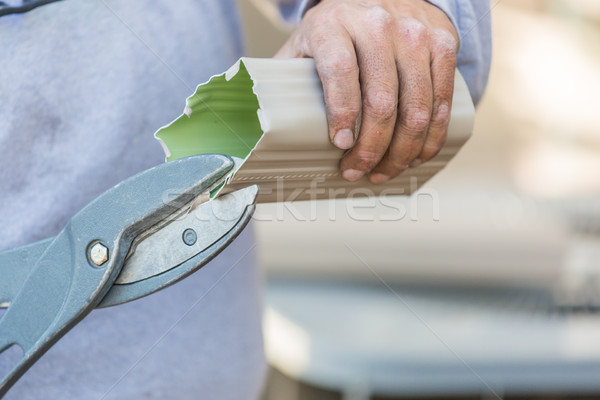 Worker Cutting Aluminum Rain Gutter With Heavy Shears Stock photo © feverpitch