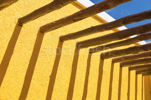 Abstract Wood Post Beams and Bright Yellow Wall Against Blue Sky Stock photo © feverpitch