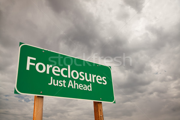 Foreclosures Green Road Sign Over Storm Clouds Stock photo © feverpitch