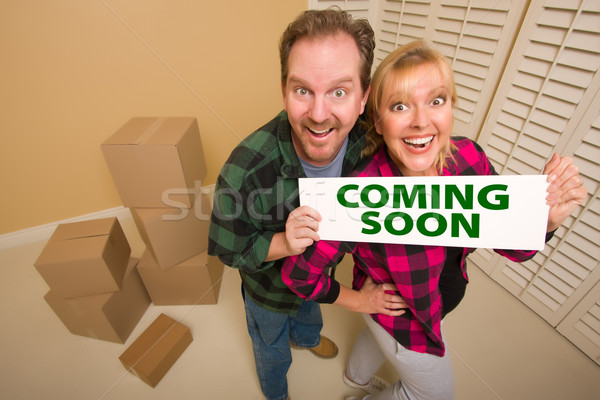 Goofy Couple Holding Coming Soon Sign in Room with Boxes Stock photo © feverpitch