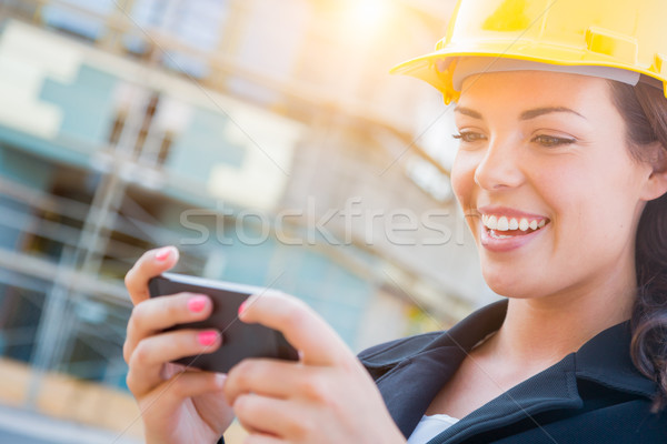 Female Contractor Wearing Hard Hat on Site Texting with Cell Pho Stock photo © feverpitch