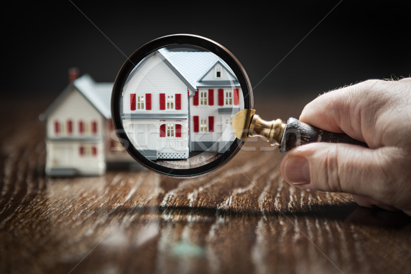 Hand Holding Magnifying Glass Up To Model Home on Reflective Woo Stock photo © feverpitch