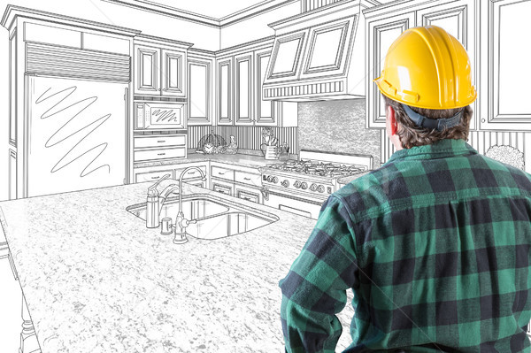 Male Contractor with Hard Hat Looking At Custom Kitchen Drawing  Stock photo © feverpitch