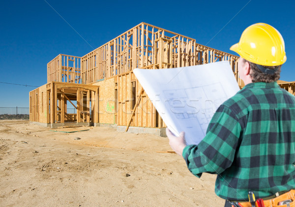 Contractor with Plans and Hard Hat Looking At New House Framing  Stock photo © feverpitch